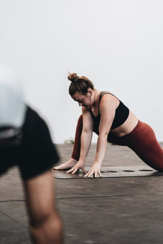 woman in black tank top and white pants doing yoga